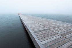 Moody scene of a foggy pier with wood panels and grey sky