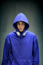 Moody serious teenage boy wearing a blue hoodie staring sullenly at the camera with earphones slung around his neck in a frontal portrait