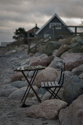 Moody shot of a chair and table on the beach of Denmark with some stones in background