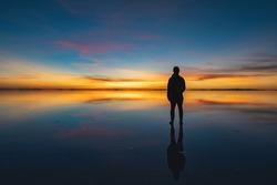 Moody shot of man looking into the horizon at dawn, solo traveller watching the sunrise at Uyuni Salt Flats (Spanish: Salar de Uyuni ), Bolivia, South America.