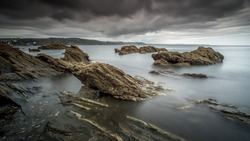 Moody sky, eroded rocks and smooth long exposure water as the tide goes out near the harbour entrance at the Cornish tourist destination of Looe in England.
