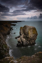 Moody sky over bay of water with sea stack on dramatic coast of Pembrokeshire in South Wales,UK.Majestic seascape and rugged rocky coastline with cliffs and coastal feature.Coastal landscape.