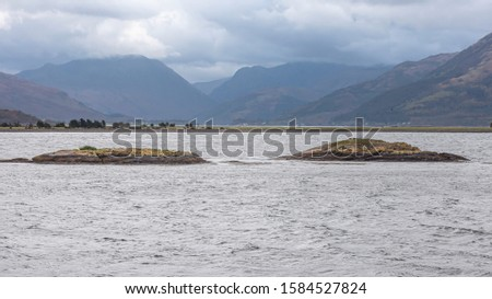 Moody sky over mountain range and Loch Etive in Scotland ,UK.Majestic view in Scottish Highlands.Two islands on lake and mountains in hazy background.Panoramic landscape image.Tranquil scene.