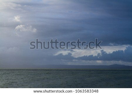 moody sky over the sea and mountains #1063583348