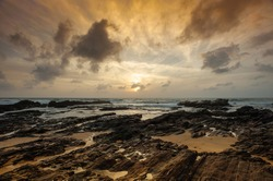 Moody sunrise over the South China Sea, east Malaysian coast. Picturesque view, rocky foreground, waves breaking along shoreline and dramatic cloudy sky.