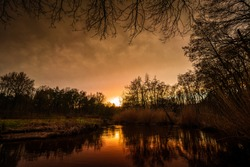Moody sunset at a Brook at Leudal, close to Heythuysen, Northern Limburg. Sun reflected in a brook. Landscape in the Netherlands.