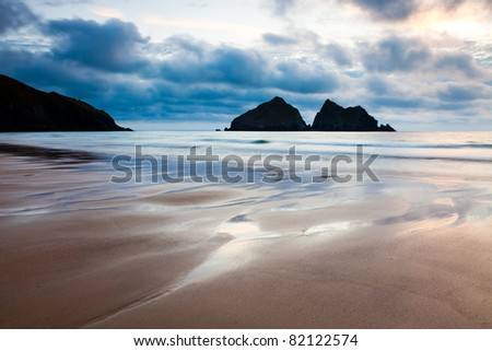 Moody sunset on the beach at Holywell Bay Cornwall England with Carters Rocks in the distance.