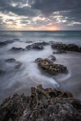 Moody sunset over water movements on beach rocks in Kenting, Taiwan