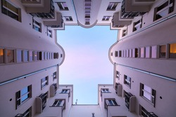 Moody symmetrical look above from backyard of an old tenement house to the roof opening with windows, walls, reflections, warm purple and blue light of the setting sun is the sky