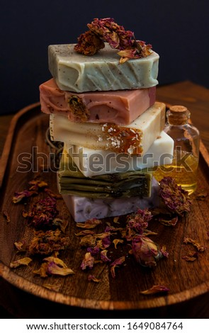 Moody view of multicolor natural bar soaps with dry flowers and roses on wooden background.