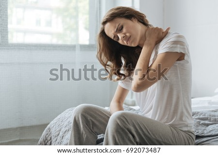 Moody young woman holding her neck