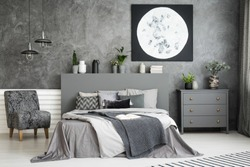 Moon art decor on the wall in a stylish grey bedroom interior with a big bed in the middle and an armchair and drawer cabinet besides. Cushions and covers on the bed. Real photo.