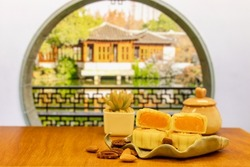 Moon cake in porcelain plate,  a traditional food, cuisine, or snack for Chinese or Asian Mid-Autumn festival. tea, blurred Chinese window and garden buildings in background.