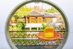 Moon cake in porcelain plate a traditional food, cuisine, or snack for Chinese or Asian Mid-Autumn festival. dry flowers and Chinese garden in background.