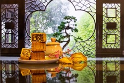 Moon cake in porcelain plate,  with  dry red flower,  blurred Chinese garden and window in background. a traditional food, cuisine, or snack for Chinese or Asian Mid-Autumn festival