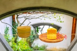 Moon cake in porcelain plate,  with tea, dry red flower, window in Chinese garden with leaves and tree in background, a traditional food, cuisine, or snack for Chinese or Asian Mid-Autumn festival