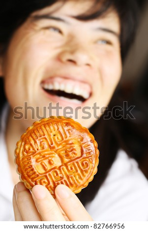 Moon cakes- Narrow focus picture of a beautiful Asian girl eating a moon cake, the traditional food of the Chinese mid-Autumn festival