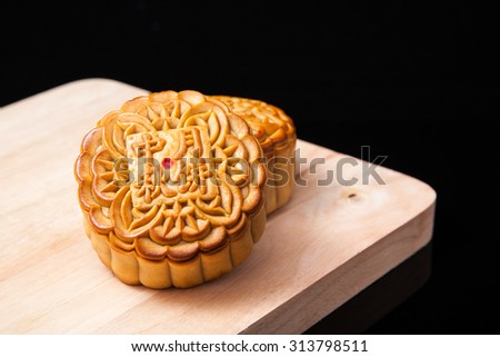 Moon cakes on wooden plate for the chinese Mid-Autumn festival on black background