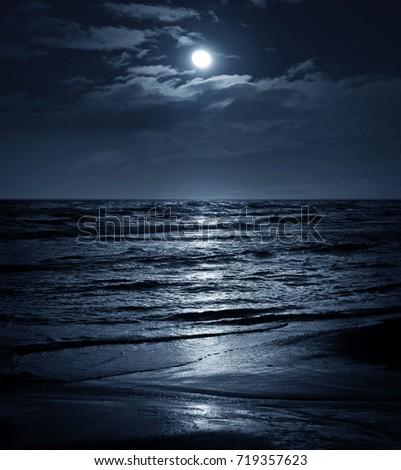 Moon in night sky over moonlit sea water. Travel background.