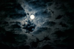 Moon in night sky with full moon. Concept of spooky, horror, Halloween theme and mystery. Dramatic clouds in the moonlight from full moon.
