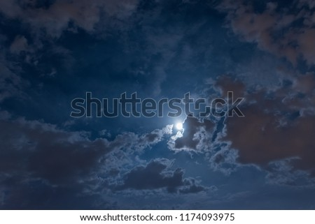 Moon in the night sky among the clouds