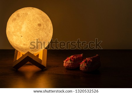 moon lamp and baby slipper on wooden table #1320532526