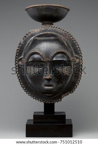 MOON MASK, 1880s, Baule peoples, Ivory Coast, Africa, sculpture, wood. Round wooden mask has a oval face edged by a zigzag border and topped with a cup. Its facial features include crescent shaped eye