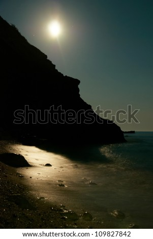 Moon night on the sea with waves and rocks.