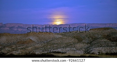 Moon rising over the Sierra del Carmen Mountains, Mexico. Seen from banks of the Rio Grande river in Big Bend National Park, Texas, United States.
