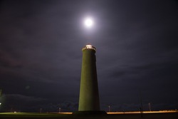 Moon shining over lighthouse in Iceland