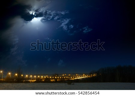 Moon with clouds in the night sky. Car highway lit lanterns. Landscape photographed in the winter in Russia. #542856454