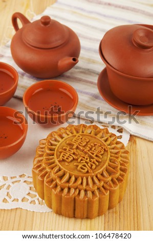 Mooncake and tea set on table. Mooncake traditionally eaten during the Mid-Autumn Festival. Chinese word on mooncake means single yolk lotus paste