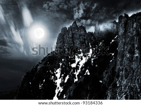moonlit night and clouds on night sky in the mountains