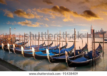 Moored gondolas in a row in evening light in Venice, Italy