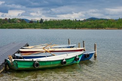 moored rowing boats on a jetty on a lake with scenic view of mountains and clouds in the background