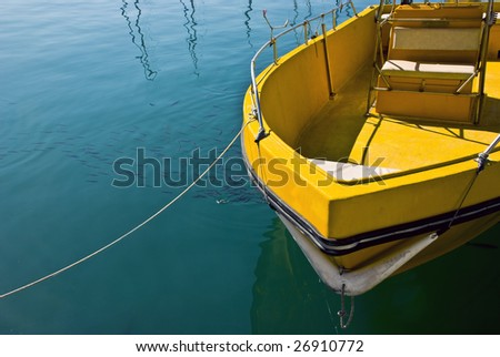 Moored yellow boat in a marina water area