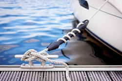 Mooring at a pier/ A white yacht moored with a line tied around a metal fixing on the quayside.