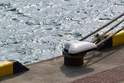 Mooring bollard and mooring ropes against the background of sea waves with sunlight glares