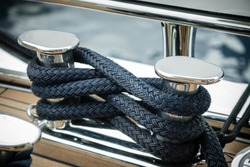Mooring lines wrapped around a big stainless steel cleat of a superyacht at dock