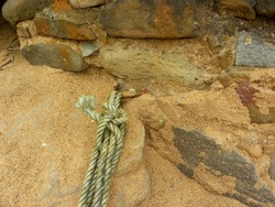 Mooring ring on the pier. Twisted nautical rope and rusty metal ring  . Marine knotted yarn for sail boat mooring.