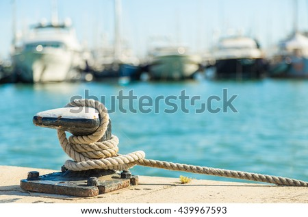 Mooring rope and bollard on sea water and yachts background #439967593