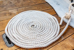 Mooring rope rolled into roll rings on a wooden board of an old boat.