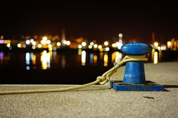 Mooring rope with a knotted end tied around a cleat on a cement pier/ Nautical mooring rope,Abstract blurred night view of city wharf lights, inverted image and coastline skyline as background.