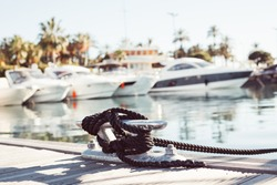 Mooring yacht rope with a knotted end tied around a cleat on a wooden pier against marina view