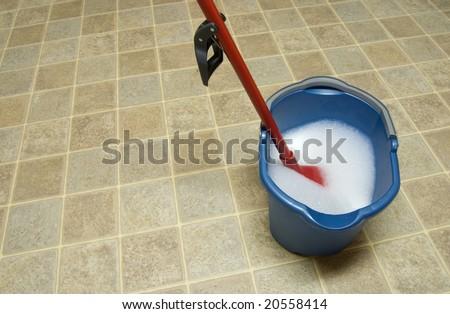 Mop and mop bucket on linoleum floor