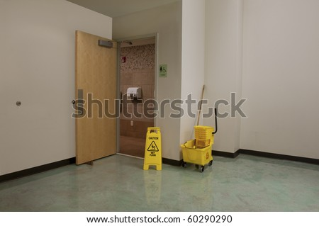 Mop bucket and caution sign outside the open door of a Women's Restroom that is being cleaned