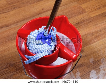 mop in red bucket with water for cleaning floors