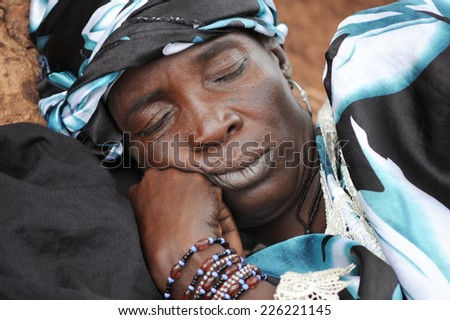 MOPTI, MALI, AFRICA - AUGUST, 26, 2011 African woman sleeping after a day of work in the market of Mopti