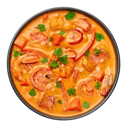 Moqueca with Fish and Shrimps in black bowl isolated on white. Brazilian sea food curry dish with coconut milk and vegetables. Top view