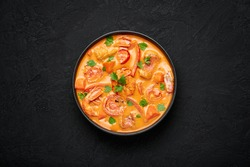 Moqueca with Fish and Shrimps in black bowl on dark slate table top. Brazilian sea food curry dish with coconut milk and vegetables. Top view